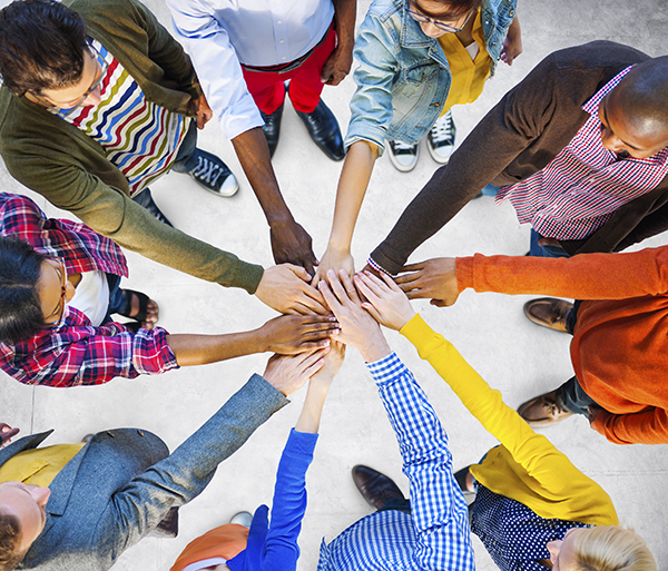 Photo of people in a circle with their hands in the middle