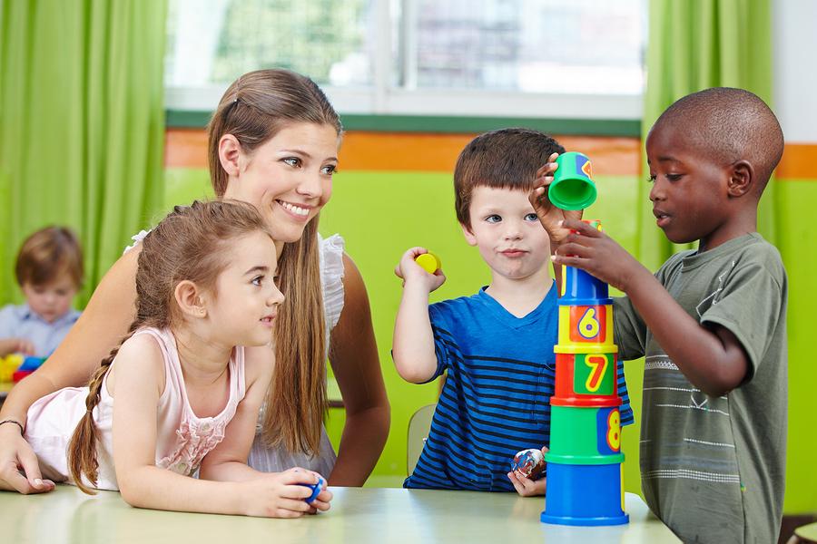 Children with nursery teacher building tower in a kindergarten g
