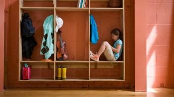Girl (6-7) sitting in hallway coat rack in school, side view