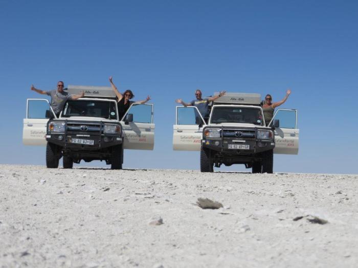 vier personen zwaaien uit twee jeeps