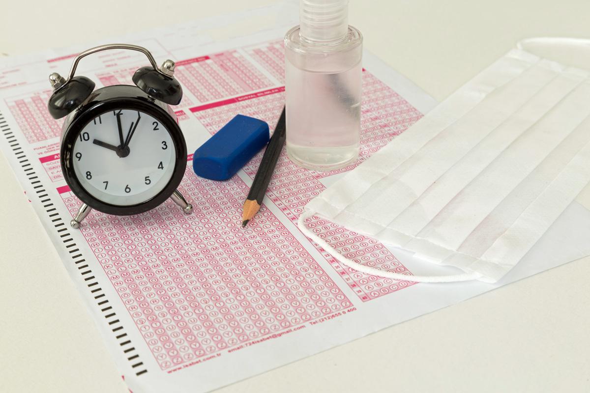 Image of standardized test bubble sheet, mask, clock, pencil, sanitizer, and eraser