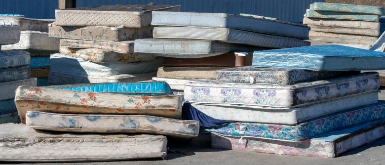 Dirty used mattresses piled at a recycling site. (Noel V. Baebler via Shutterstock)