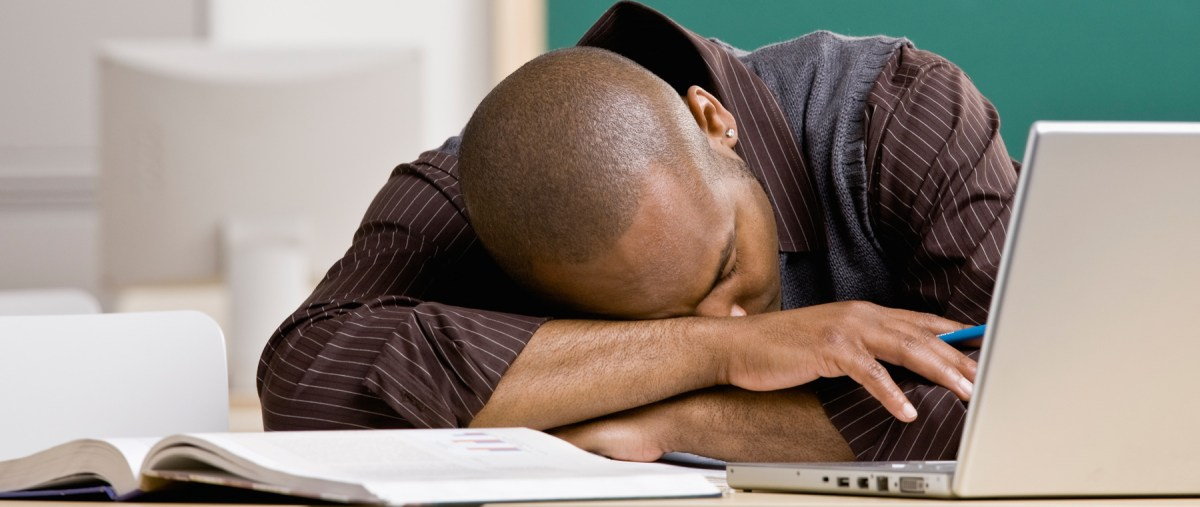 Exhausted teacher laying on desk in school classroom.