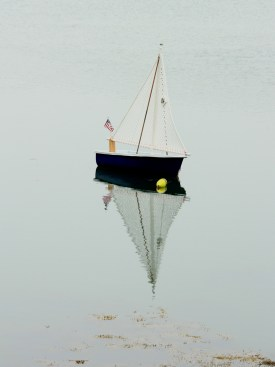 A small rigged sailboat in an inlet on the way to Stonington on Deer Isle