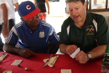 Coach Tom teaches the Cuban coach how to play dice baseball.