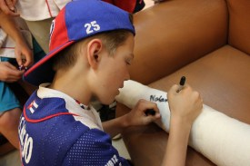 Nolan Simon signs the cast of his teammate Carter Monks, who injured his knee in Tuesday's game.