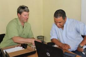 Vermont Coach Tom Simon teaches Evian Guerra, a prominent Cuban journalist, how to play dice baseball, a game Simon created.