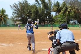 A Cuban player reaches for a high fastball.