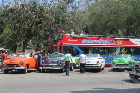 A row of colorful classic cars line the street in the Capital District of Havana.