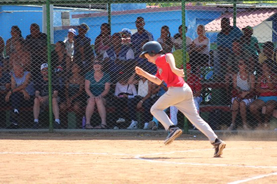 Running to first base in the game against the provincial team.