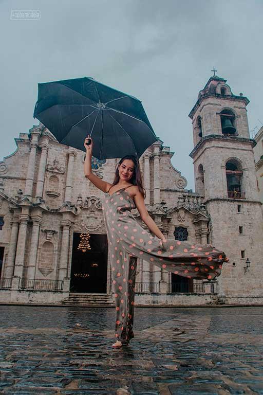 fotografia artistica a quinceañera en body con circulos rojos sosteniendo un paraguas azul frente a la catedral de la habana en un dia nublado