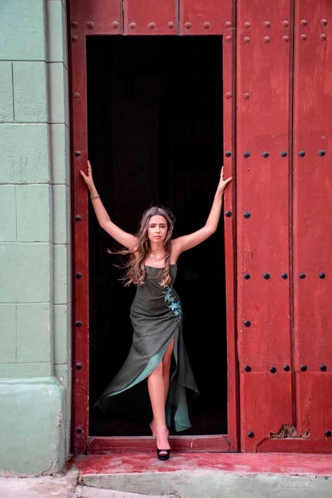 fotografia a quinceañera cubana en vestido verde en el umbral de un portón de caoba de la habana vieja