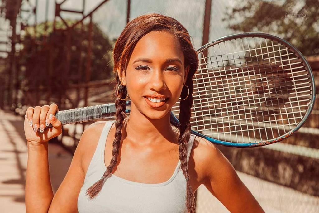 quinceañera cubana con trensas sosteniedo una raqueta al hombro