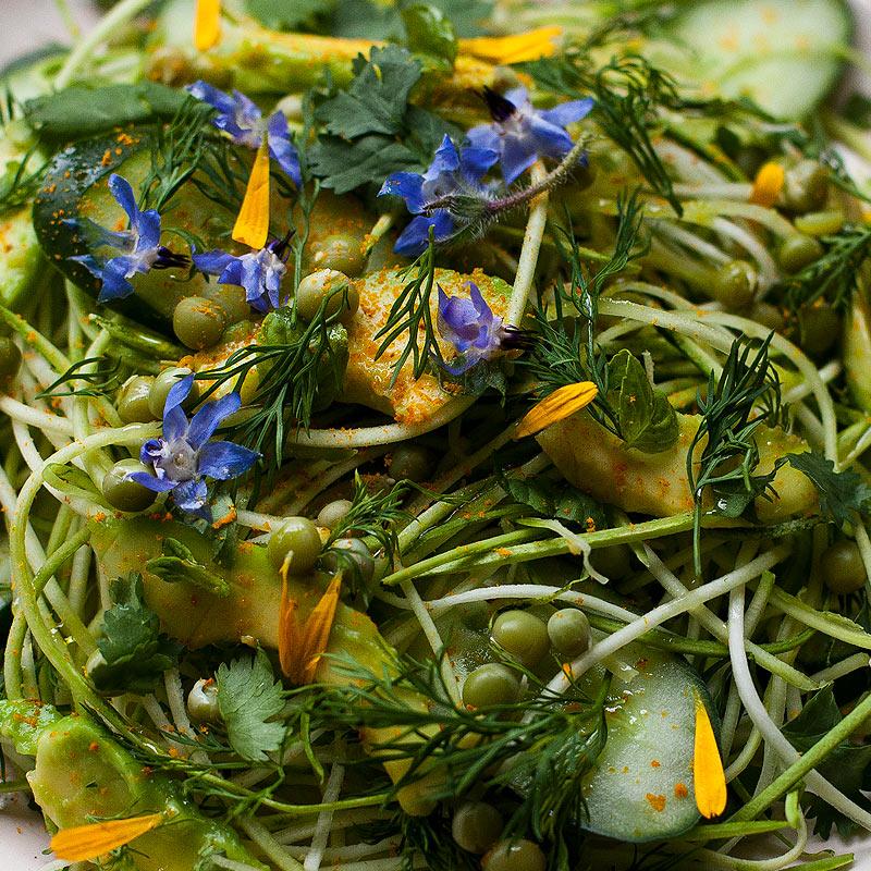fideos de calabacín con aguacate, flores lobelias, guisantes y pétalos de crisantemo