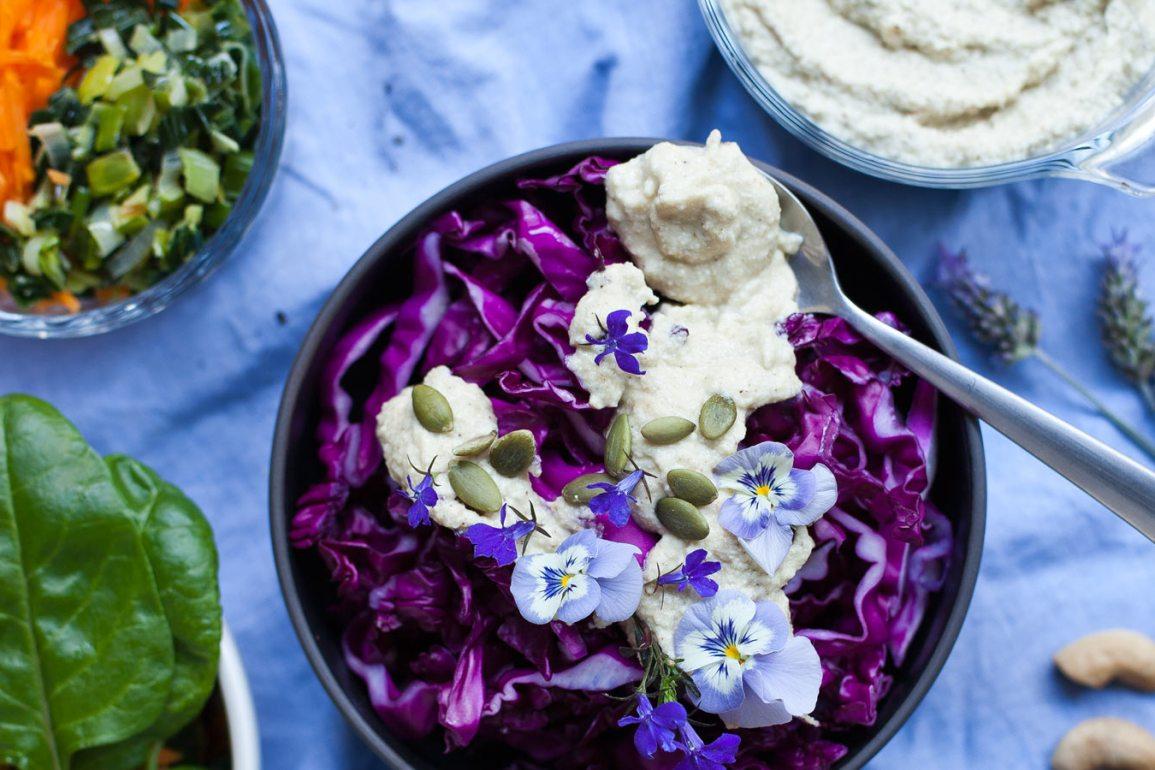 Ensalada de repollo colorado con dip de anacardos, semillas de calabaza y flores comestibles