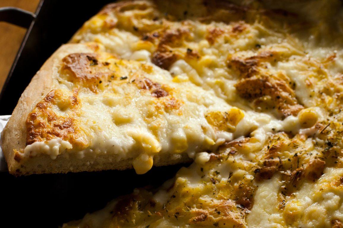 Porción de pizza de choclo y salsa blanca siendo sacada