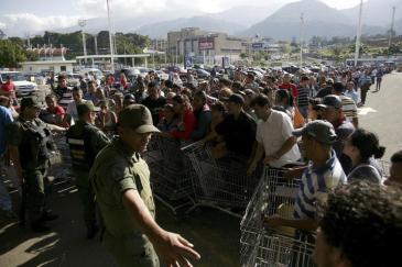 National guards control the entrance of a private supermarket as people line up to enter in San Cristobal
