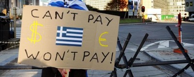A Protestor holds a placard with a Greek flag during a demonstration outside of an EU summit in Brussels on Sunday, Oct. 23, 2011. Greece's prime minister George Papandreou is pleading with European leaders in Brussels to act decisively to solve the continent's debt crisis. At a summit Sunday, the leaders are expected to ask banks to accept huge losses on Greek bonds to ease the pressure on the country, and to raise billions more in capital to weather those losses. (AP Photo/Geert Vanden Wijngaert)