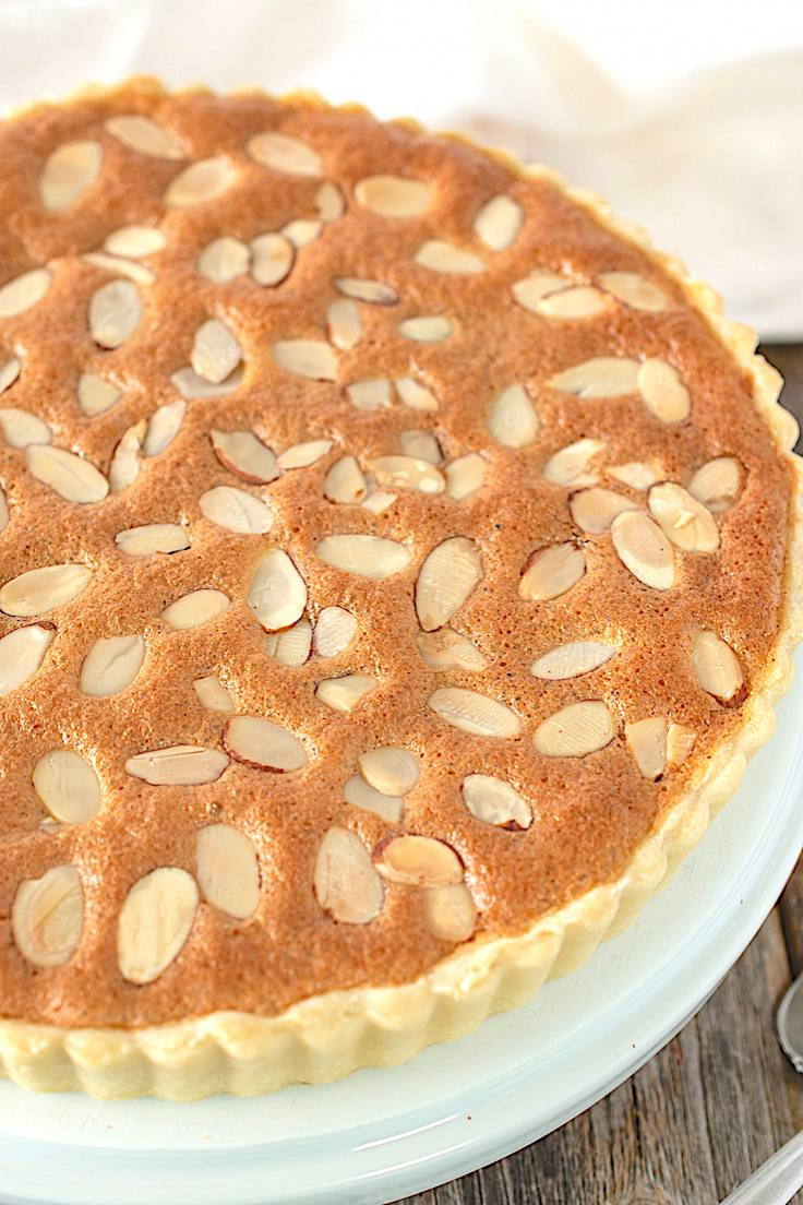 A closeup of a classic bakewell tart showing the sliced almond in the topping