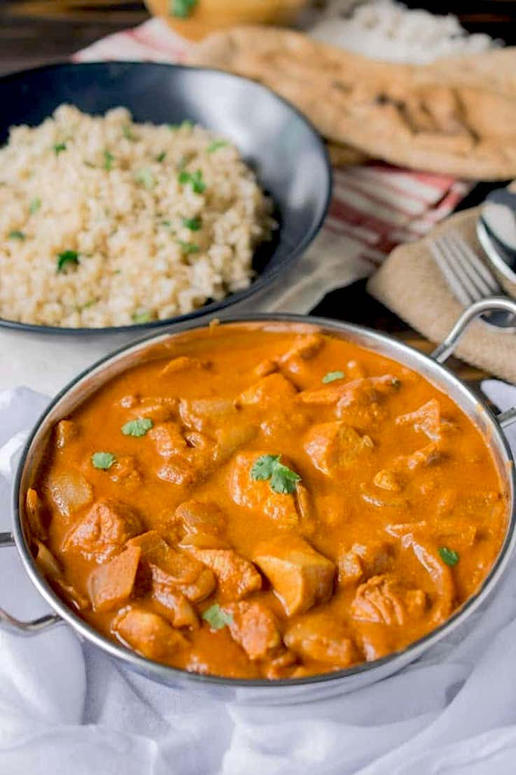 Chicken tikka masala ready to be eaten with rice and naan bread