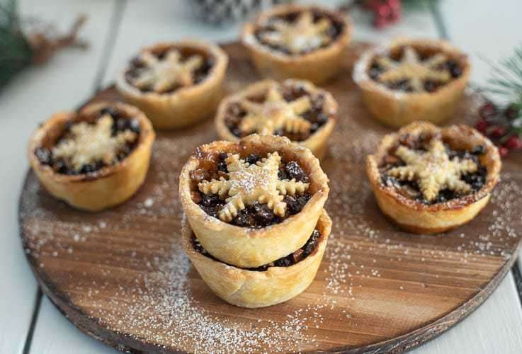 Christmas Sweet Mince Pies on a wood board dusted with powdered sugar
