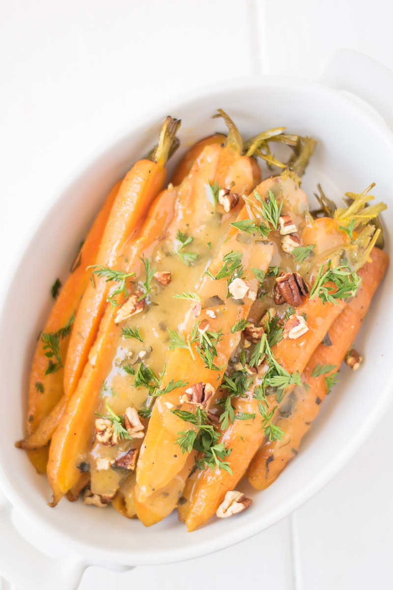 A bowl of slow cooked carrots with pecans and herbs