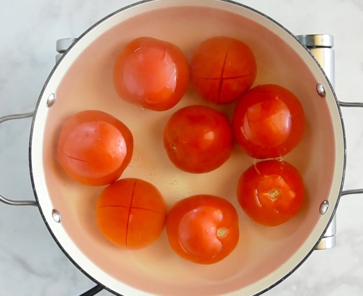Tomatoes in simmering water to help remove the skins