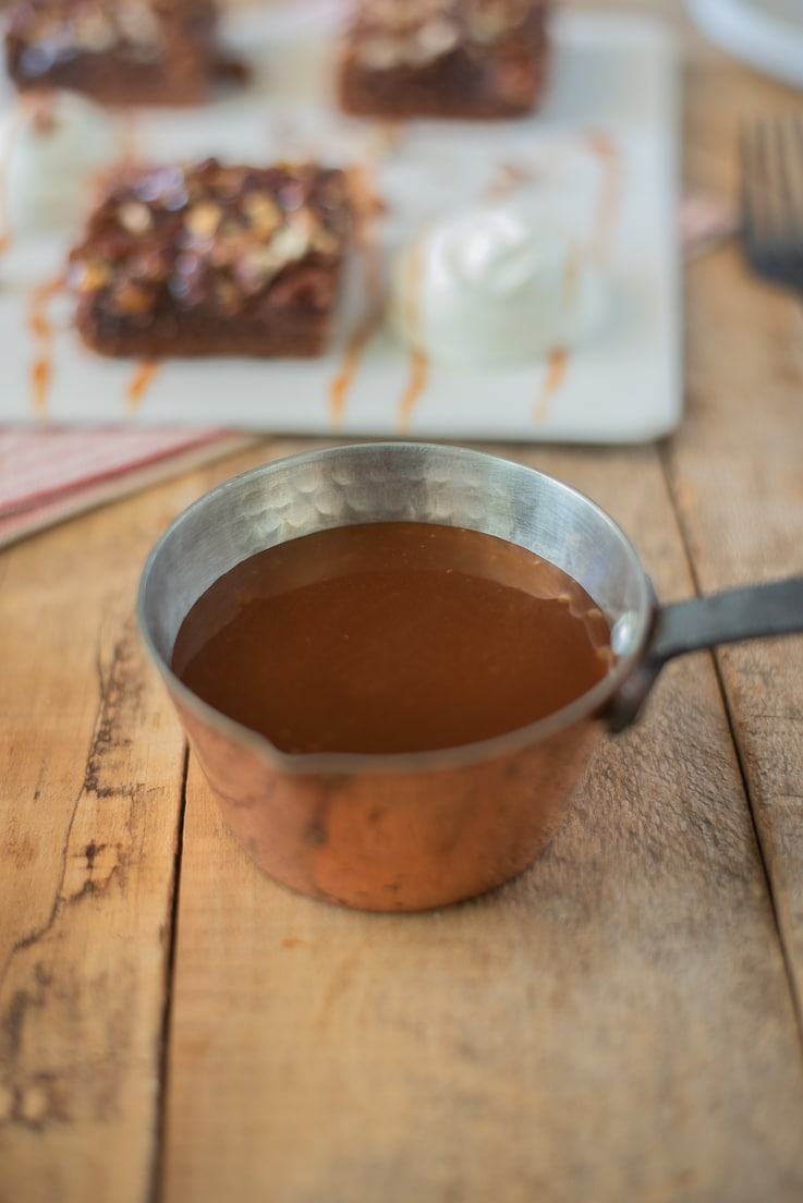 A small copper pan of caramel sauce with brownies in the background