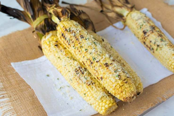 Grilled Parmesan, garlic and basil corn on the cob is a delicious use of sweet, seasonal corn. Sweet corn is grilled then topped with fresh Parmesan, a butter made with roasted garlic and fresh basil for the best barbecue side dish.