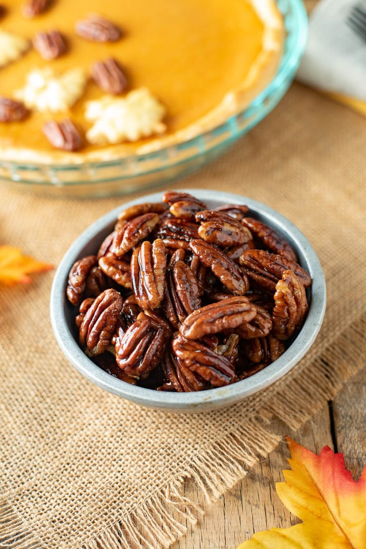 Maple Glazed Pecans in a silver bowl with a sweet potato pie