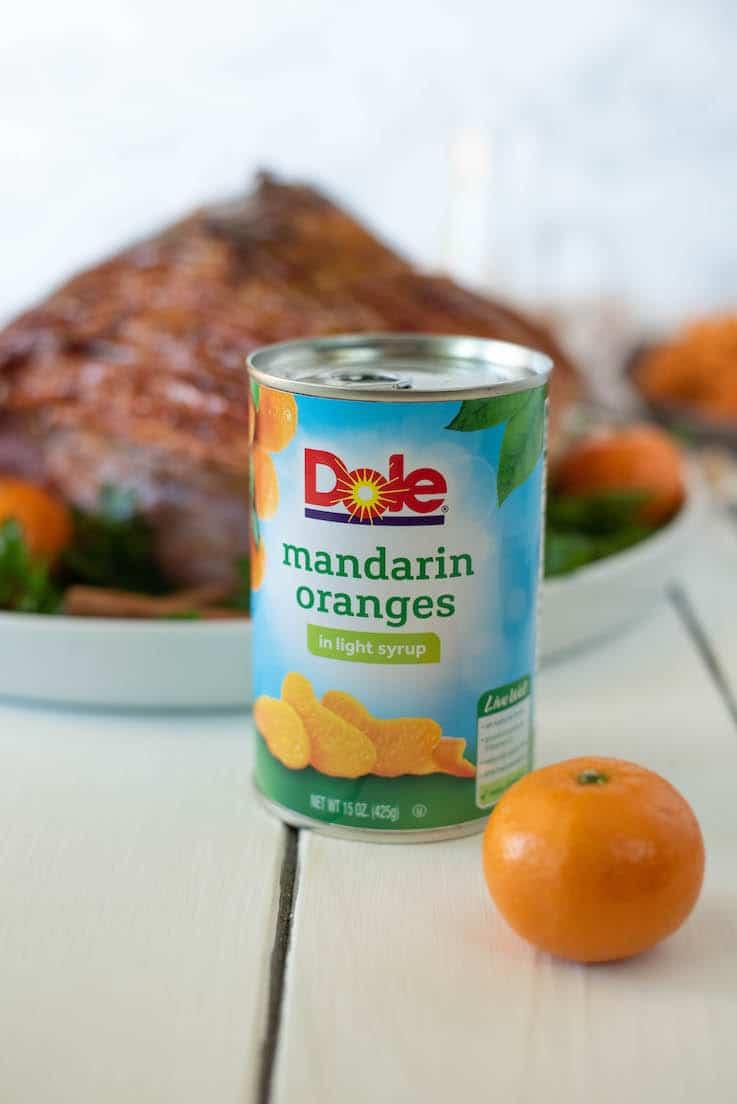 A can of Dole mandarin oranges with a mandarin orange