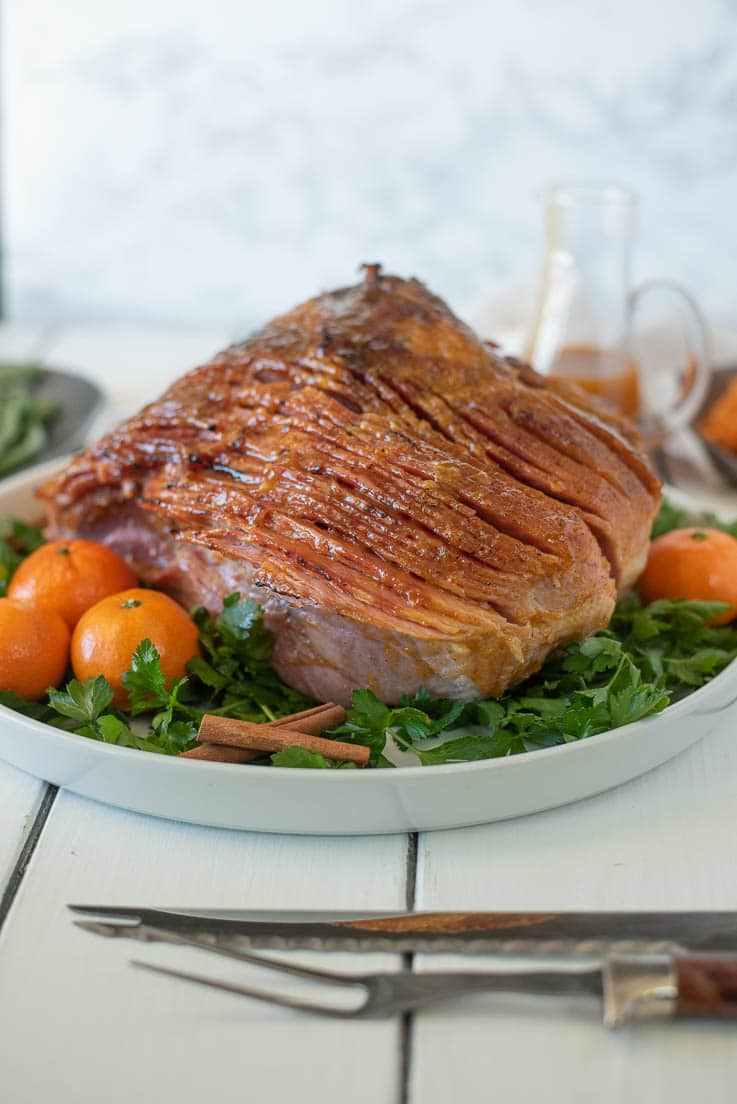 Mandarin Orange Spiced Glazed ham on a white serving platter garnished with greens and mandarin oranges