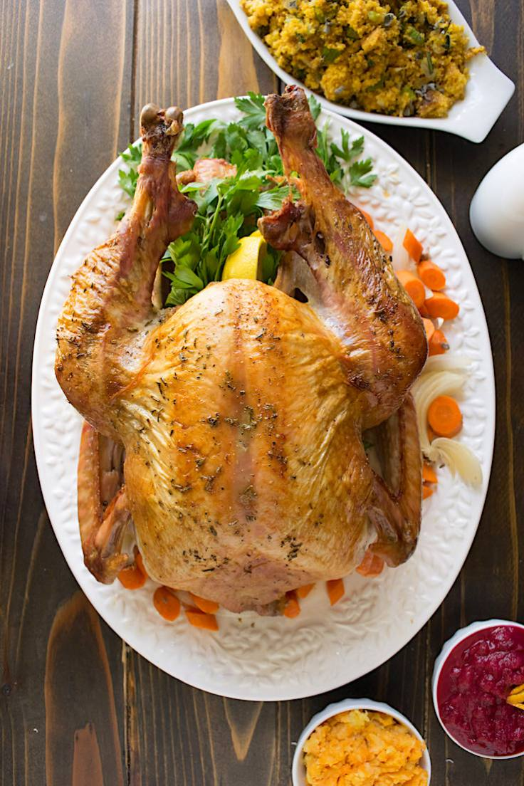 A perfectly roasted turkey surrounded by carrots and parsley