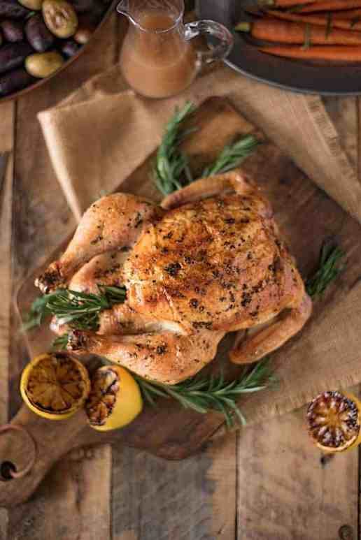 Rosemary roasted chicken with delicious gravy is everything you want when enjoying a roast chicken dinner. Brushed with butter, fresh rosemary, salt and pepper, the chicken is roasted over vegetables and stock so the gravy is made right in the pan while the chicken roasts.