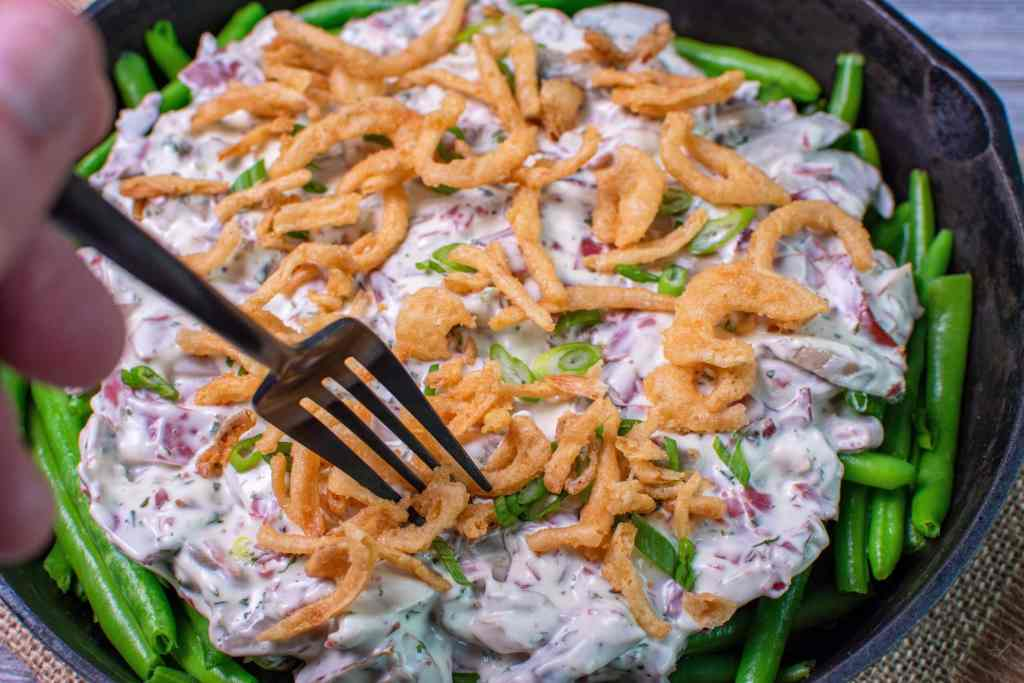portion of cream chipped beef green bean casserole topped with crispy onions
