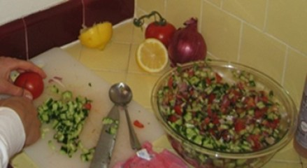 making an Israeli salad with red onion, cucumbers, tomato, and lemon juice