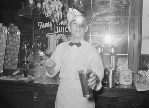 Soda Jerk in a Texas Soda Fountain is making a malted milkshake, round about 1939. Borden's Malted milk in the background.