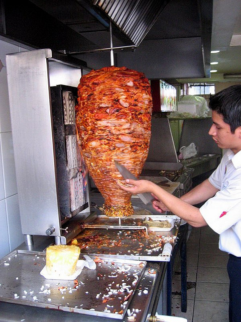authentic tacos al pastor being shaved from spit