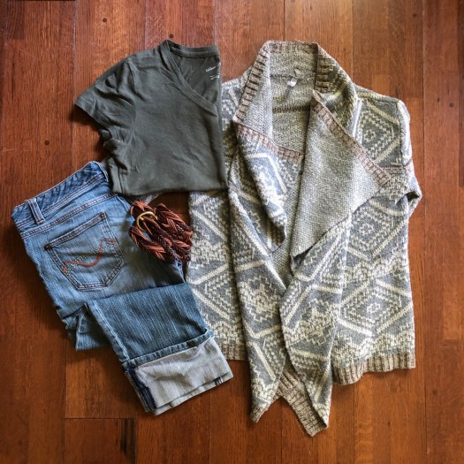 A pair of jeans, a shirt, a belt, and a sweater are laid out on the floor for display.