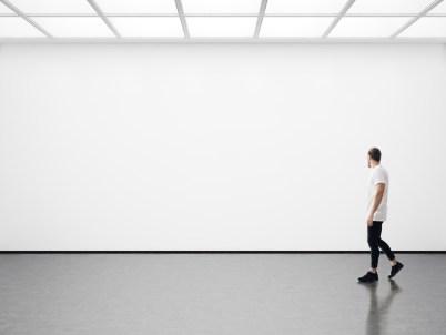 A man wanders an empty art gallery.