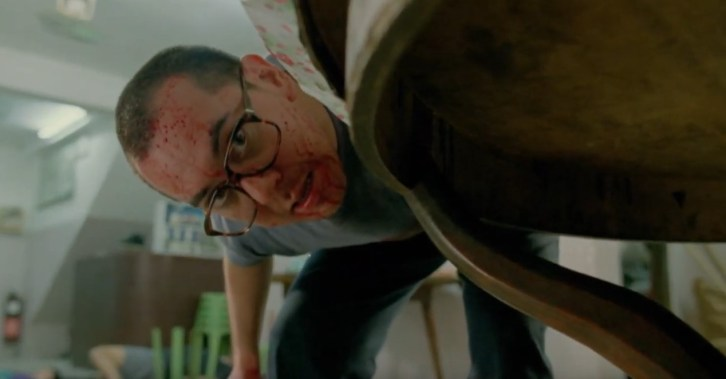 A screen shot taken from the 1993 horror film, The Untold Story. It shows a bloodied man peering underneath a table while brandishing a large knife.