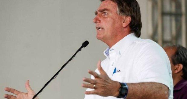 Presidente discursa em púlpito. ele usa camisa branca e gesticula com as mãos.