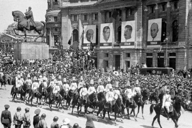 Paradă pe Calea Victoriei în ziua de 23 august 1945, cu ocazia sărbătoririi a un an de la momentul în care România a trecut de partea forţelor aliate. În fundal se poate vedea alăturarea portretului regelui Mihai cu cel al lui Stalin.