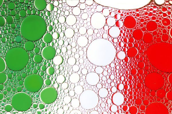 Italian flag. Close up of oil drop on water surface.