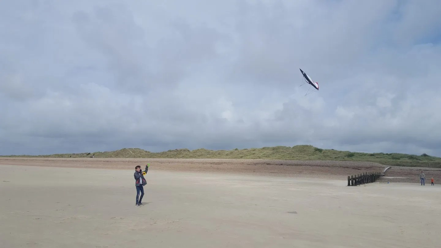 Kite flying on wide sandy beach