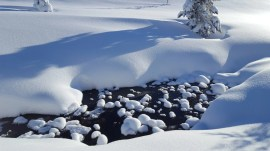 Snow mounds icy stream