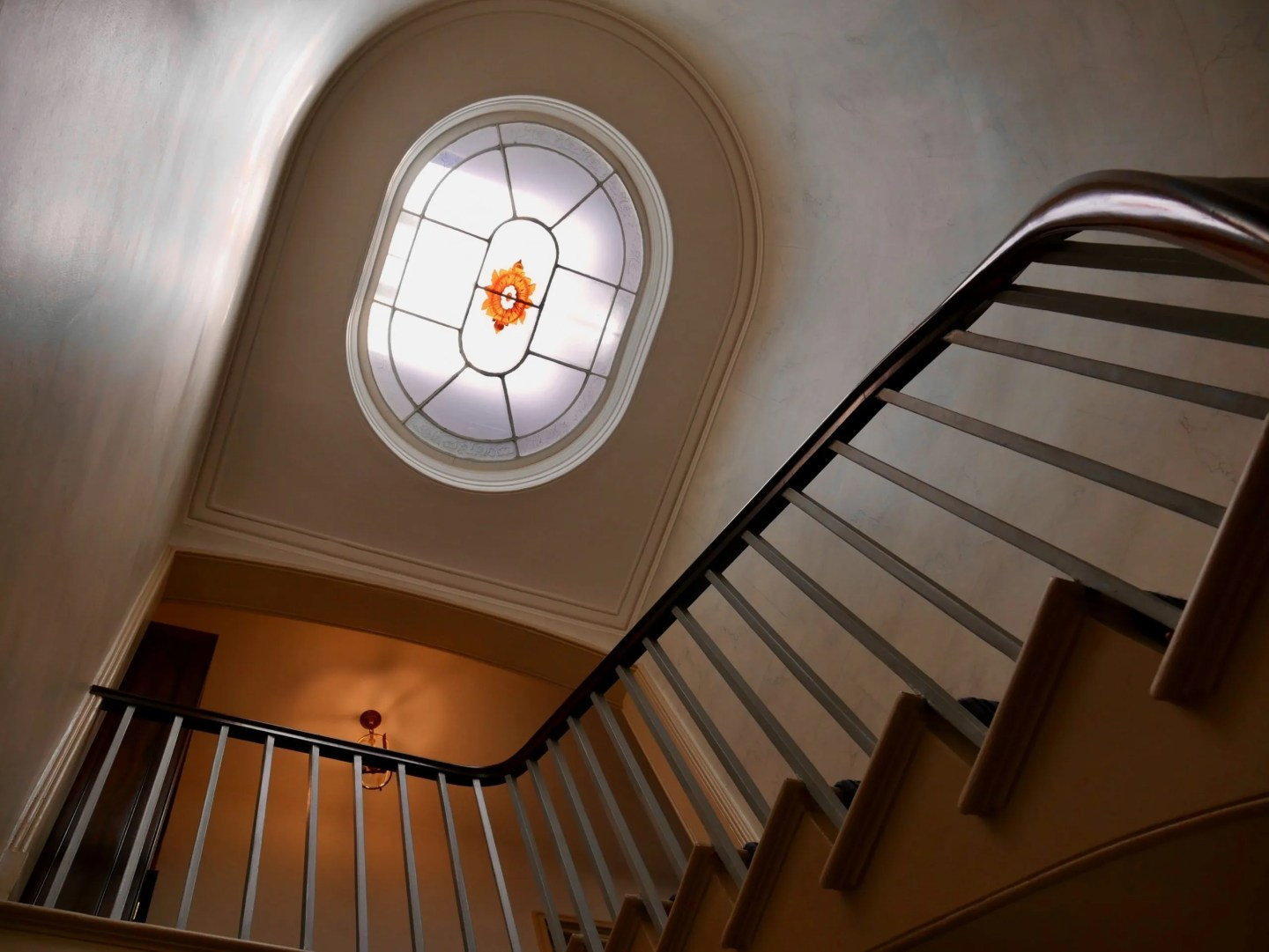 Looking up a stairwell to a fancy stair lantern light