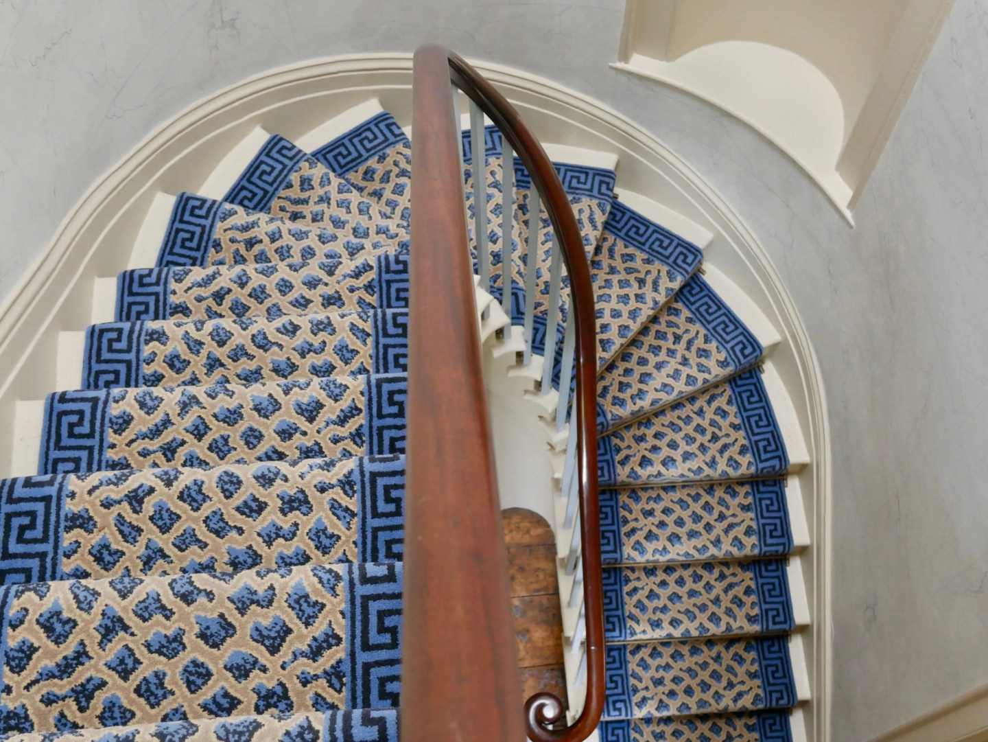 Looking down a curving staircase with blue carpet at Turner's House