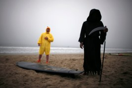 Owolo, dressed as the Grim Reaper, and Petrulis, dressed as a chicken, prepare to compete in the ZJ Boarding House Halloween Surf Contest in Santa Monica