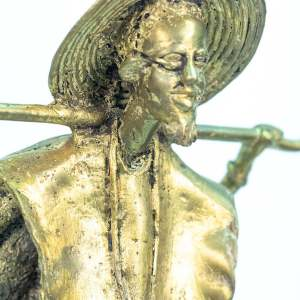 figurine, brass man holding staff over his shoulders, closeup